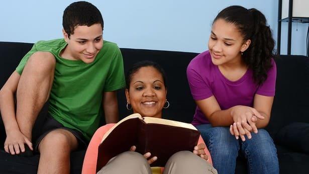 educazione dei figli: mamma e figli leggono la parola di Dio insieme