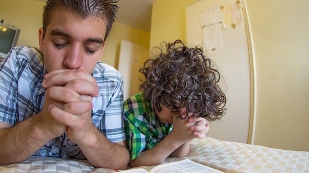 educare i figli: un padre e un figlio pregano a Dio insieme